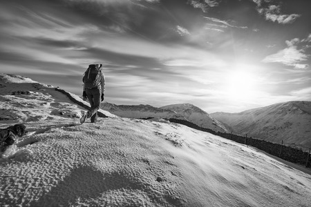 snow covered mountains: Hiker walking their dog over snow covered mountains in the UK. Grain and colour styling applied Stock Photo