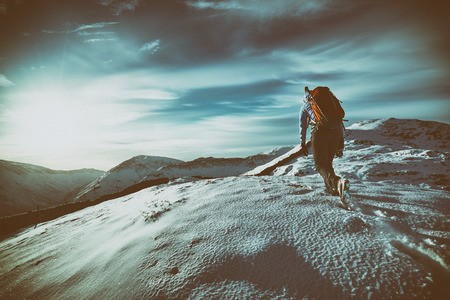 snow covered mountains: Hiker walking over snow covered mountains in the UK. Grain and colour styling applied