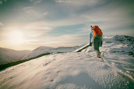 Hiker walking over snow covered mountains in the UK. Grain and colour styling applied
