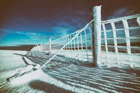 low temperature: A frozen wire fence below the summit of Geal-charn Mor, Cairngorms in the Scottish Highlands, UK. Added grain and colour styling. Stock Photo
