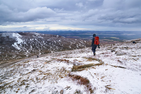 cairn: A hiker descending Meall a Bhuachaille Cairn in the Cairngorms in the Scottish Highlands, UK. Stock Photo