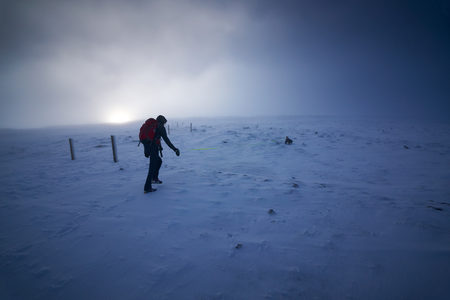 cairn: A hiker and their dog approaching the summit of Cairn Gorm as the sun fights through the cloud, Scottish Highlands, UK.