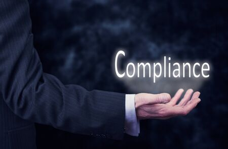 comply: Businessman pressing an Compliance concept button.
