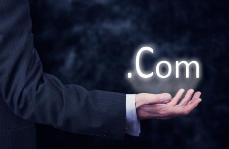 web portal: Businessman pressing an .com concept button. Stock Photo