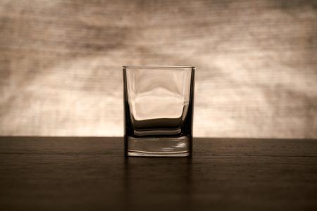 bar top: An empty whisky glass on a wood bar top.