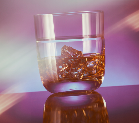 manlike: A glass of whisky with ice on a modern reflective bar top and blue background. Stock Photo