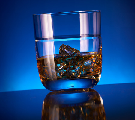 bar top: A glass of whisky with ice on a modern reflective bar top and blue background. Stock Photo
