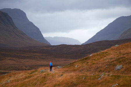 A hiker walking along the West Highland way into Glencoe, Scottish Highlands. Stok Fotoğraf