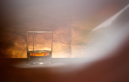 manlike: A glass of whisky on a wood bar top. Stock Photo