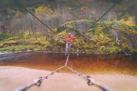 traverse: A hiker crossing the wire footbridge over the Water of Nevis. Glen Nevis, Scottish Highlands. Added colour styling and grain.
