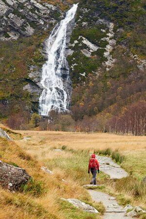 scottish female: A hiker approaching An Steall waterfall, Water of Nevis. Glen Nevis, Scottish Highlands.