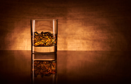 bar top: A glass of whisky with ice on a reflective bar top.