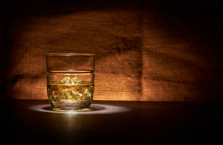 bar top: A glass of whisky with ice on a wood bar top. Stock Photo