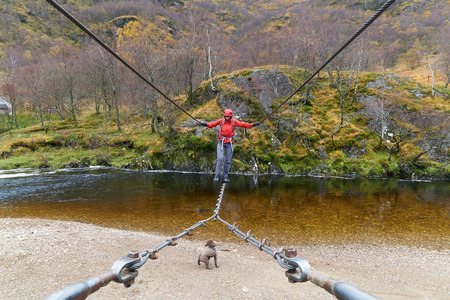 scottish female: A hiker crossing the wire footbridge over the Water of Nevis. Glen Nevis, Scottish Highlands. Stock Photo