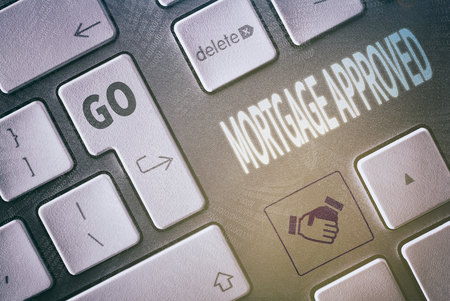 underwriter: Close up of a keyboard with a Mortgage Approved concept. Stock Photo