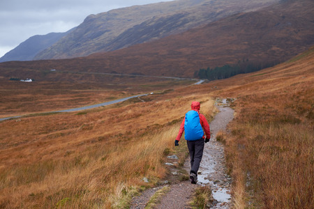 scottish female: A hiker walking along the West Highland way into Glencoe, Scottish Highlands. Stock Photo