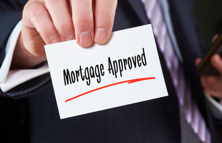 homeownership: A man holding a Business card Mortgage Approved Concept