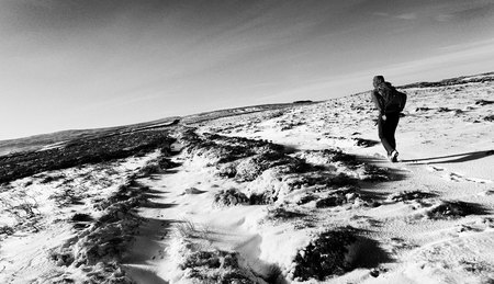 winter escape: Hiker walking over Edmondbyer Common, England, UK.