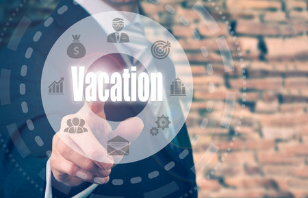recuperation: A businessman selecting a Vacation Concept button on a clear screen. Stock Photo