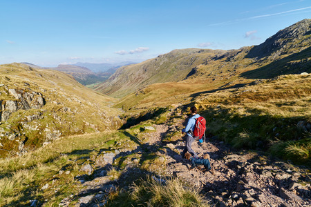 gill: A hiker walking down towards Seathwaite, Grains Gill from Scafell Pike in the English Lake District. UK. Stock Photo