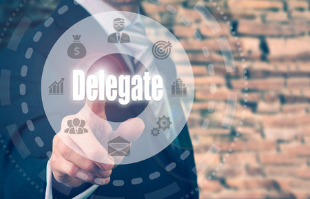 appoint: A businessman selecting a Delegate Concept button on a clear screen. Stock Photo