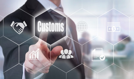 importation: A businessman selecting a Customs Concept button on a clear screen. Stock Photo