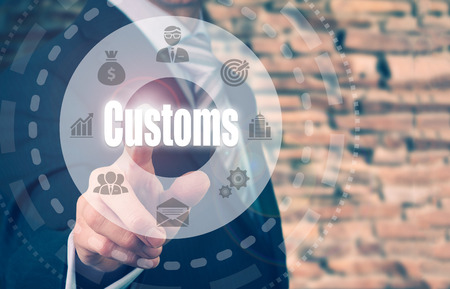 A businessman selecting a Customs Concept button on a clear screen. Stock Photo