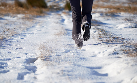 winter escape: The legs of a hiker and their dog walking through a snow covered winter landscape. Edmondbyer Common, England, UK.
