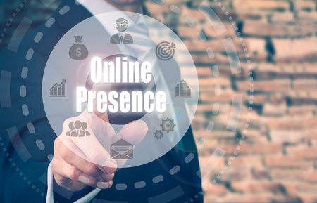 presence: A businessman selecting a Online Presence Concept button on a clear screen. Stock Photo