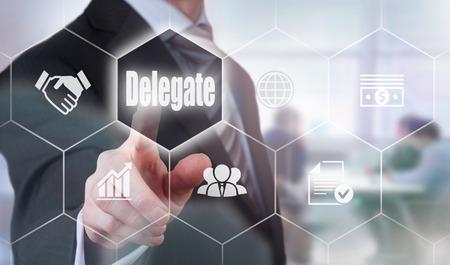 delegar: A businessman selecting a Delegate Concept button on a clear screen. Foto de archivo