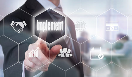 implement: A businessman selecting a Implement Concept button on a clear screen.