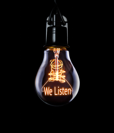 competencies: Hanging lightbulb with glowing We Listen concept.