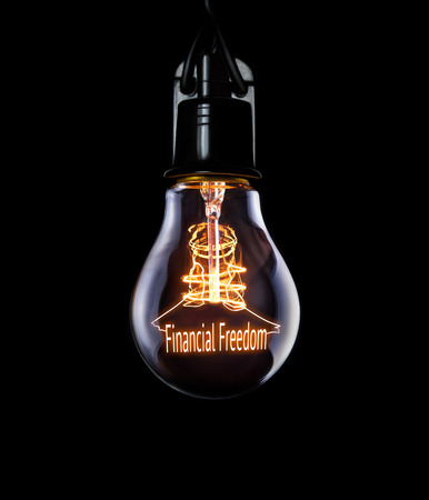 frugal: Hanging lightbulb with glowing Financial Freedom concept. Stock Photo