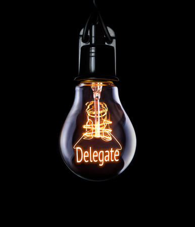 Hanging lightbulb with glowing Delegate concept. Stock Photo