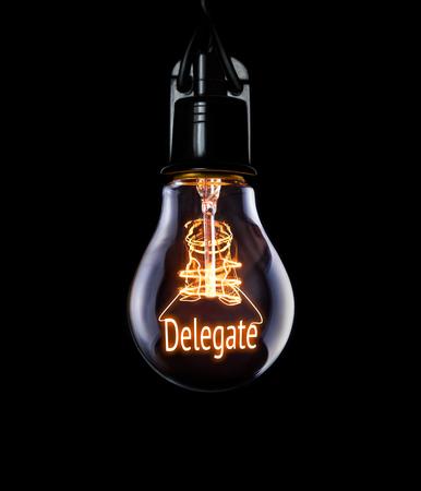 delegar: Hanging lightbulb with glowing Delegate concept. Foto de archivo