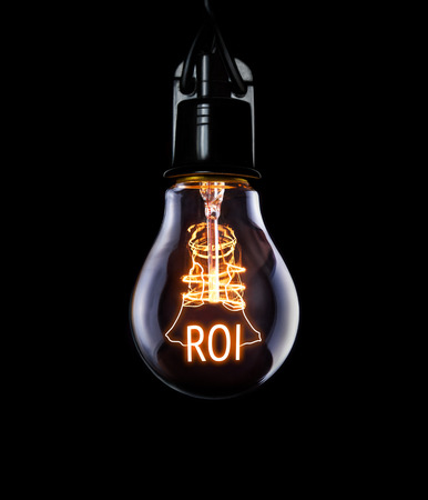 Hanging lightbulb with glowing Return on Investment concept.