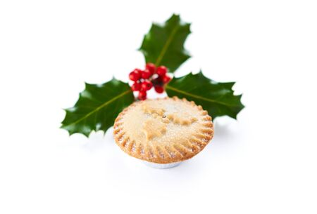 Close up of a Christmas Mince Pie and holly sprig isolated on a white background