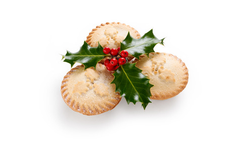 Close up of Christmas Mince Pies and holly sprig isolated on a white background Stok Fotoğraf