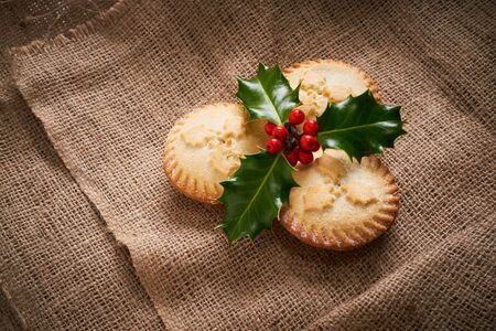 Close up of Christmas Mince Pies and holly sprig on a natural hessian background Stock Photo