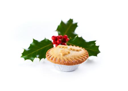 Close-up van een Kerst gehakt taart en hulst takje geïsoleerd op een witte achtergrond Stockfoto