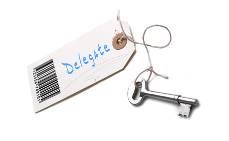 assign: A silver key with a tag attached with a Delegate concept written on it. Stock Photo