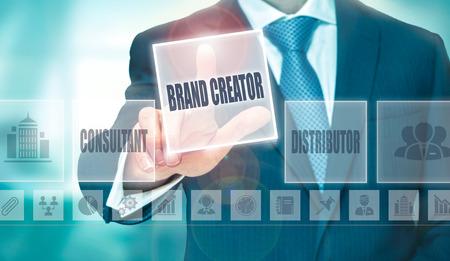 creador: Un hombre de negocios presionando un botón Creador Marca en una pantalla transparente. Foto de archivo
