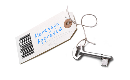A silver key with a tag attached with a Mortgage Approved concept written on it.