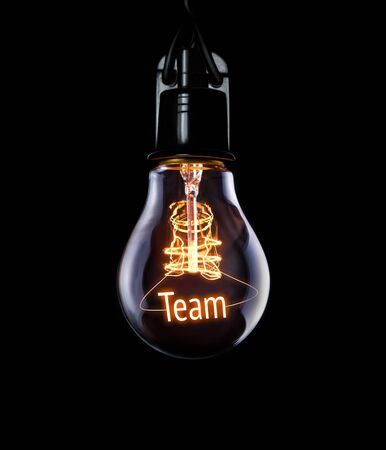 Hanging lightbulb with glowing Team concept. Stock Photo