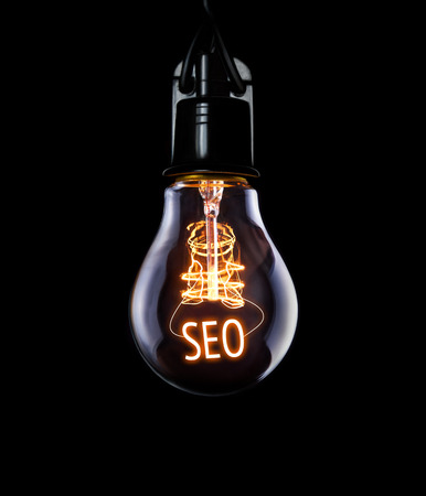 meta data: Hanging lightbulb with glowing SEO concept.