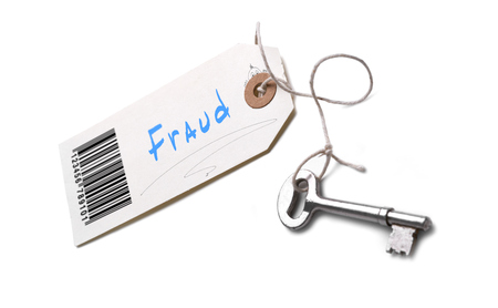 A silver key with a tag attached with a Fraud concept written on it.