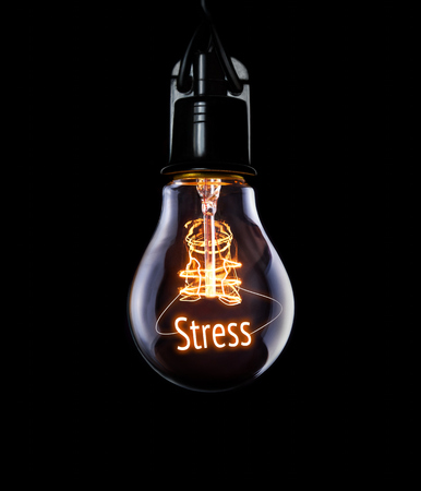 Hanging lightbulb with glowing Stress concept.