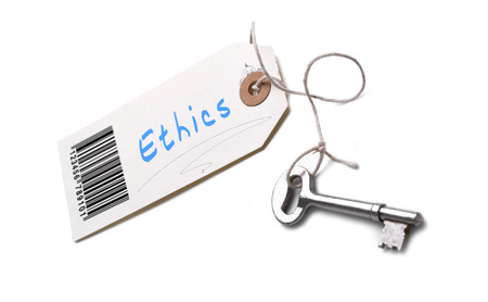 ethos: A silver key with a tag attached with a Ethics  concept written on it.