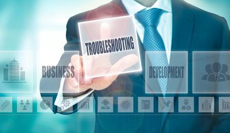 troubleshooting: Un hombre de negocios presionando un botón Solución de problemas en una pantalla transparente.