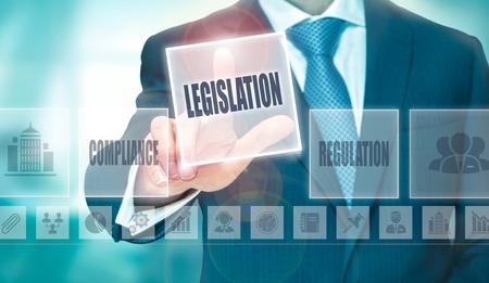 legislating: A businessman pressing a Legislation button on a transparent screen.